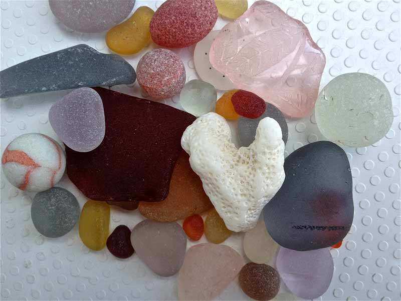 A coral heart nestles atop some rare sea glass colors